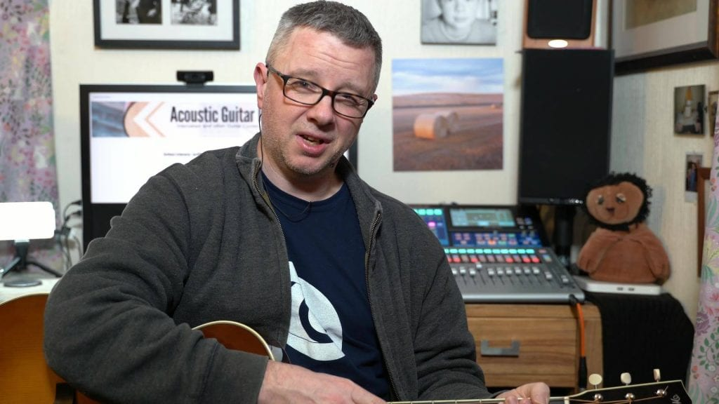 White middle aged man holding a guitar in his living room and talking to a camera